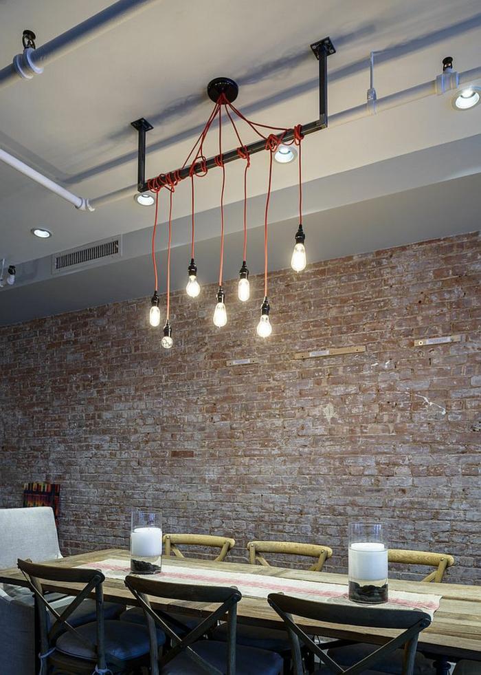 decoracion de salones, comedor estilo industrial, mesa y sillas de madera clara, pared de ladrillo, bombillas colgantes, candelas