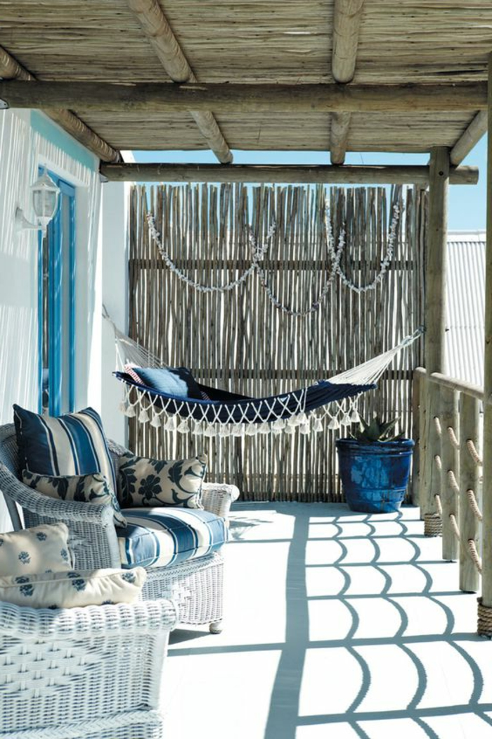 decoracion de terrazas, balcón en zona costera, muebles de rattan, cojines y hamaca en tonos azulez