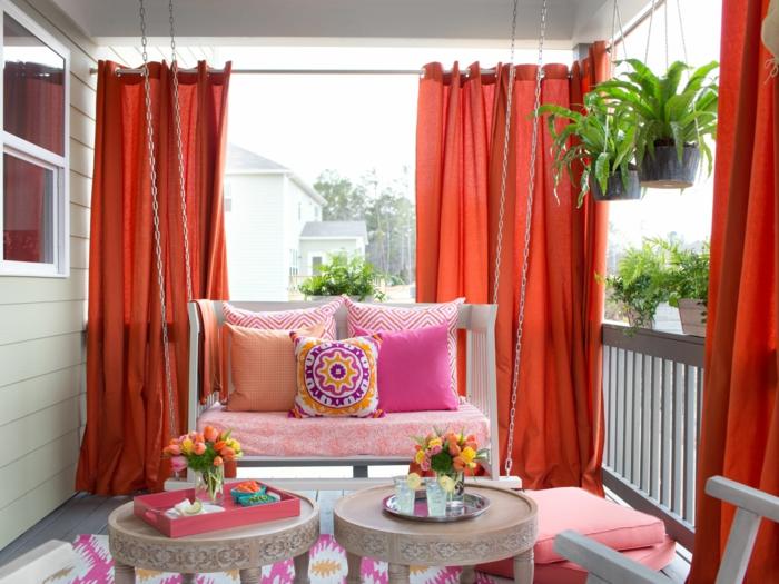 decoracion de tarrazas, balcón decorado madera blanca, cortinas rojas, mesas redondas, flores y macetas colgantes