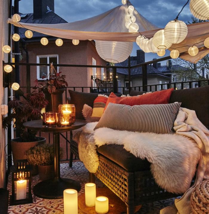 decoracion de terrazas, balcón pequeño con sofá de rattan, mesa con candelas, cojines y globos de luz