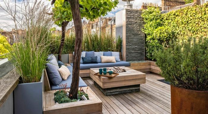 decoracion de terrazas, terraza con suelo de madera, mesa cuadrada, sofás con cojines azules y beige