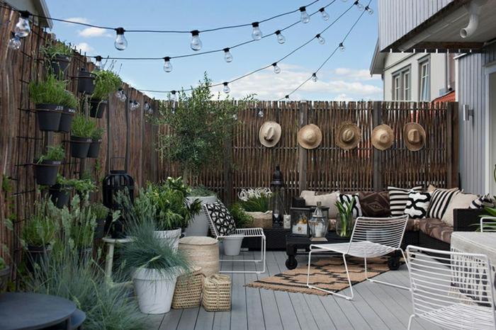 decoracion de terrazas, terraza con suelo de tarima, sillas blancas de metal, decoracion con plantas, sombreros y bombillas