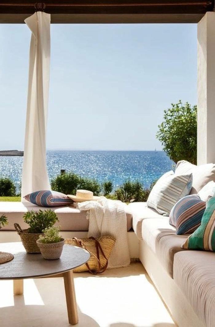 decoracion de terrazas, terraza con vista al mar, mesa redonda, sofá con cojines
