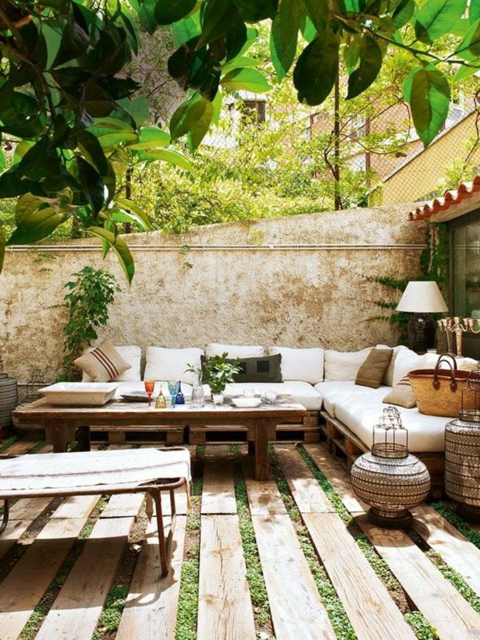 decoracion jardin, terraza con suelo de madera y césped, sofá con cojines blancos, mesa con vasos y lámpara