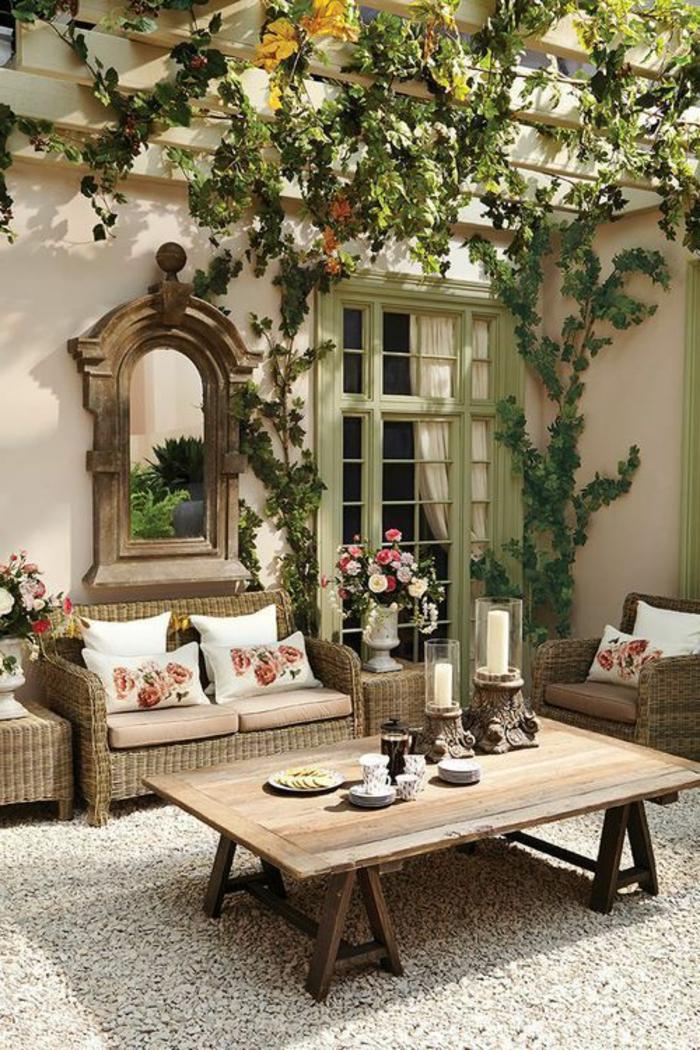 decoracion ajrdin, terraza con mesa de madera, sillones de rattan con cojines, mesa con portavelas, suelo de gravilla, espejo y plantas