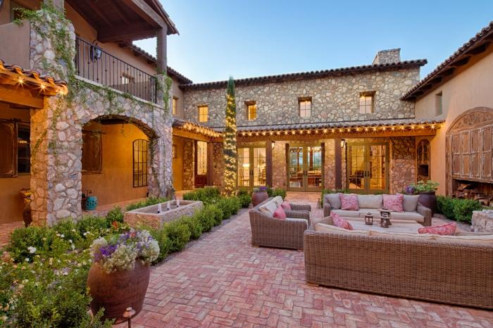 decoracion rustica, casa de piedra con bóvedas, jardñin y patio pavimentado con sillones y sofás