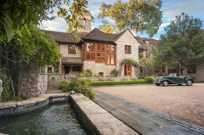 decoracion rustica, casa de piedra y madera, coche verde de jardín con fuente y árboles