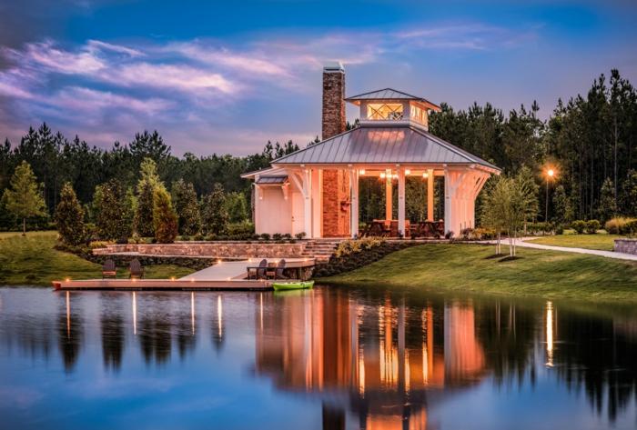 decoracion rustica, casa moderna en blanco con chimenea de piedra, patio con césped, paisaje con lago