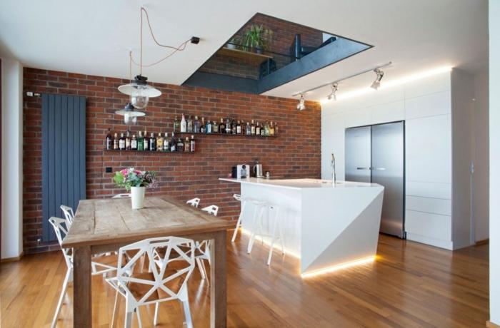 decoracion salon, comedor con mesa de madera y sillas de plástico con huecos, suelo laminado, pared de ladrillo