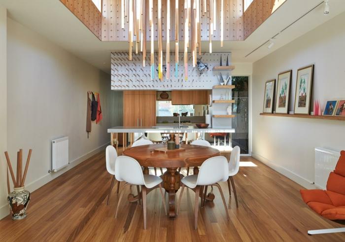 decoracion salon, mesa redonda de madera, sillas blancas, suelo laminado, cocina con salida, estanterías, cuadros