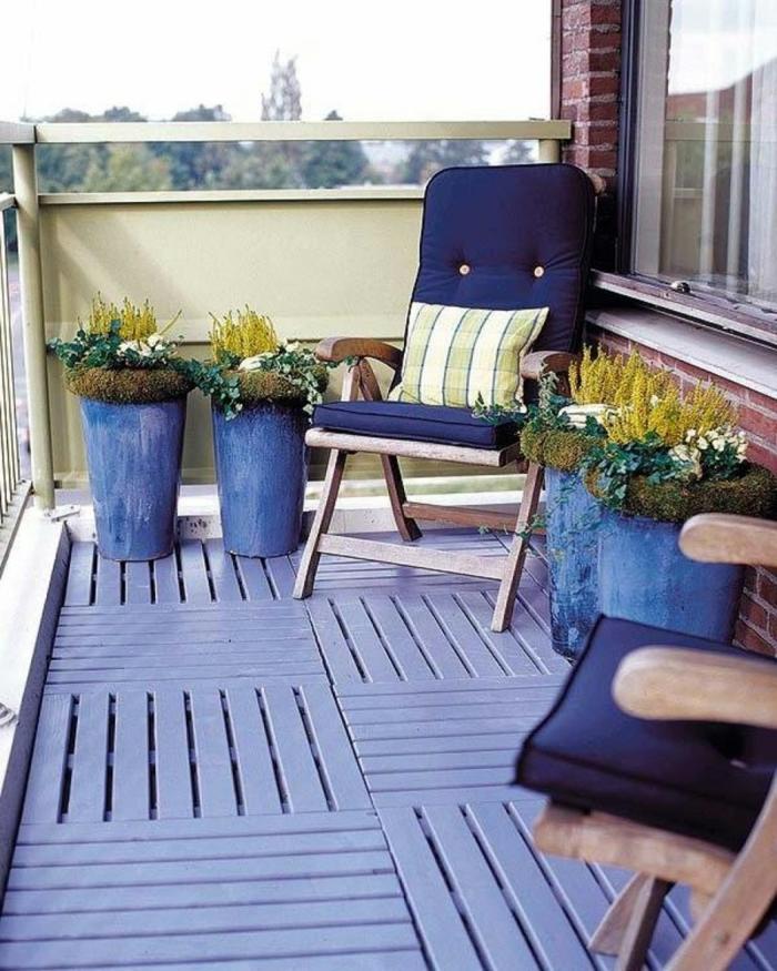 decoracion terrazas, balcón en azul con suelo de tarima, cojines y flores amarillos