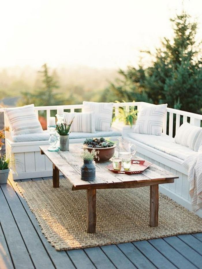 decoracion terrazas, balcon son banca blanca y cojines, mesa de madera con jarra y vasos, tapete de mimbre