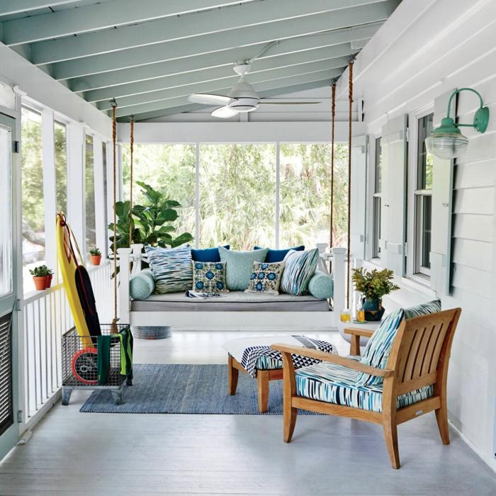 decoracion terrazas, balcon cubierto con suelo laminado, sofá y sillón, cojines en azul y tapete