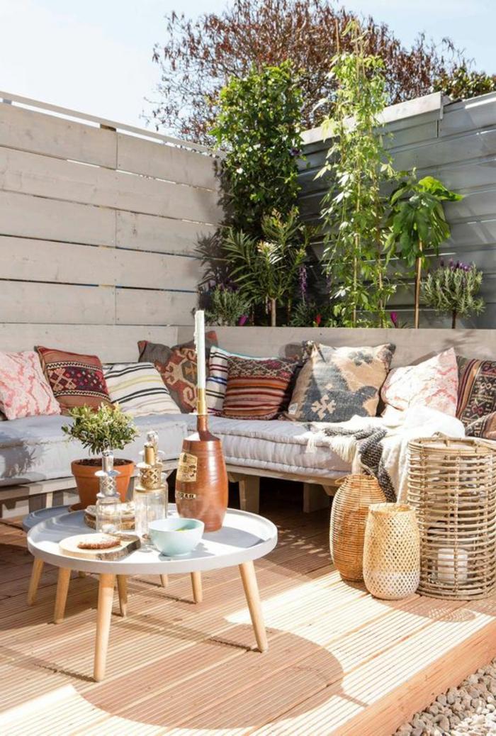 decoracion terrazas, terraza suelo de madera, sofá con cojines, mesa redonda con portavelas y plantas