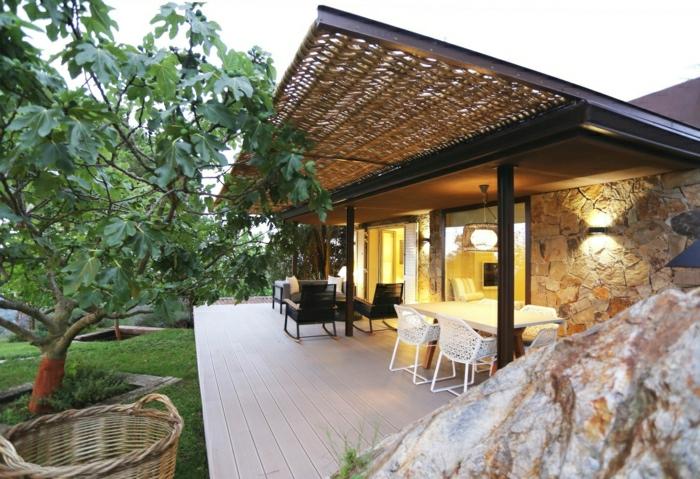 fachadas de casas rústicas, villa de madera y piedra con un piso, mesas bajo un toldo
