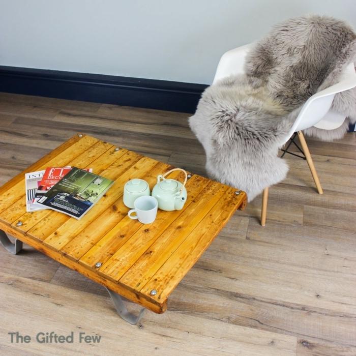 mesas con palets, silla blanca, mesa palets madera clara, revistas y tetera con tazas