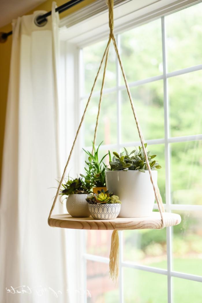 estante colgante de madera, macetas con flores verdes