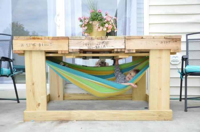 muebles de jardín con palets, mesa alta de palets con maceta de flores, hammaca con niño, dos sillas
