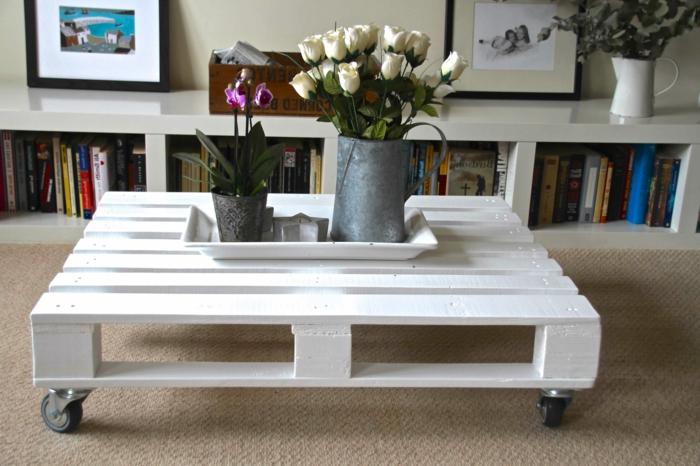 ideas con palets, mesa blanca de paltes con ruedas, meceta y jarra con rosas blancas, librería y cuadros