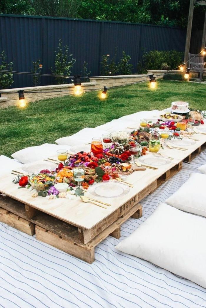 muebles de jardín con palets, mesa baja de palets con cubiertos y flores, cojines y bombillas colgantes
