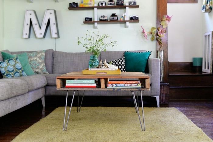 mesas con palets, mesa de madera con piedras de metal, sofá con cojines, estanterías y flores