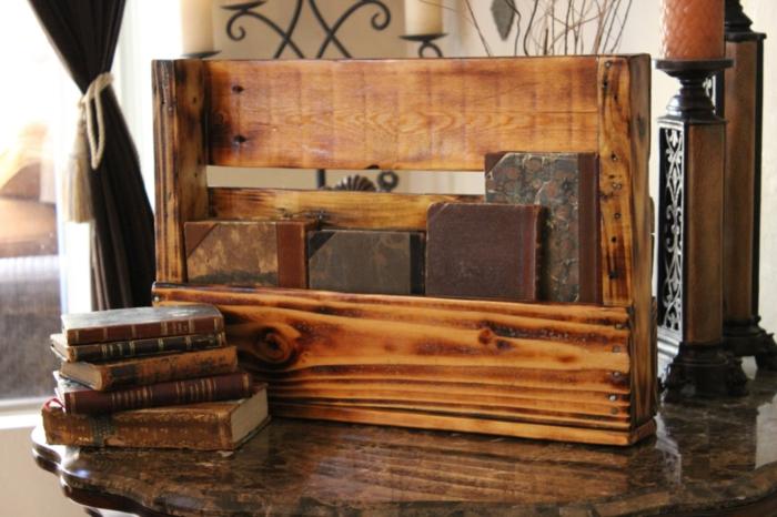 muebles hechos con palets, porta cuadernos de madera sobre mesa, libros y candelas