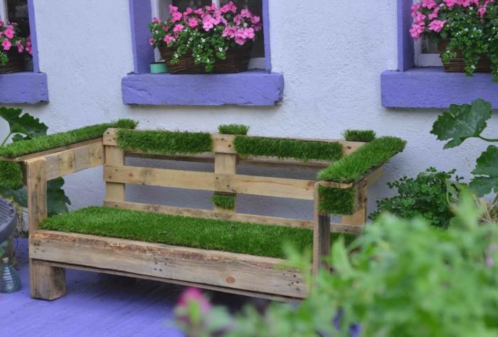 palets de madera, banca de jardín con palets y césped, ventanas con flores en rosa