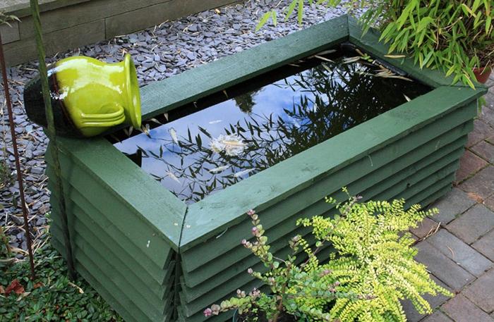 palets de madera, fuente de jardín con palets pintados en verde, plantas y jarra decorativa