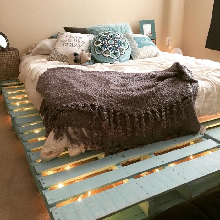 ideas con palets, cama de palets pintada en azul, colchón con cojines, porta fotos y luces