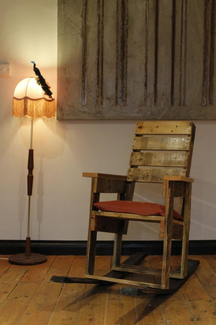 ideas con palets, sillón balancín con cojín rojo, ventana y lámpara