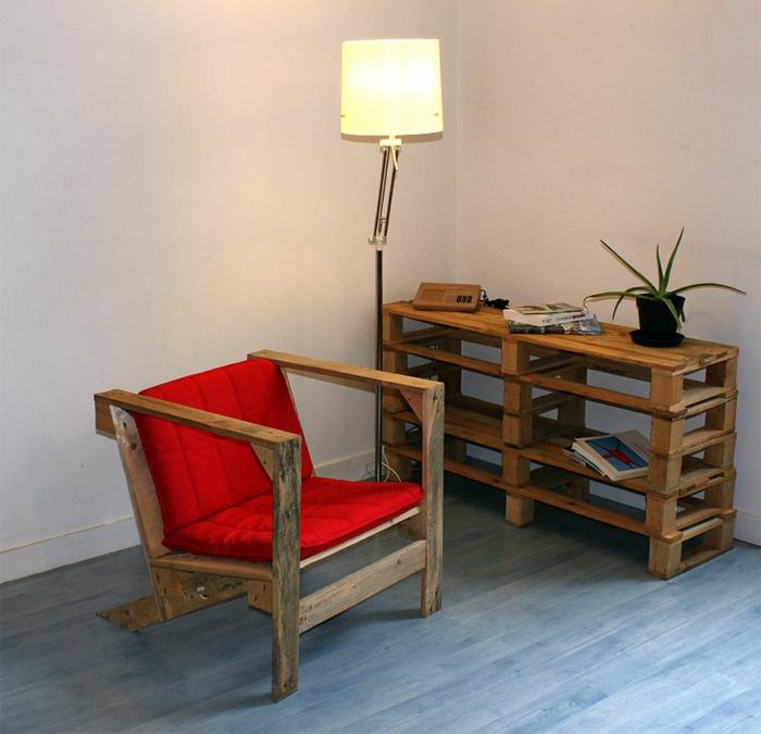 mesas con palets, sillón tapizado en rojo, mesa de palets con planta y lámpara