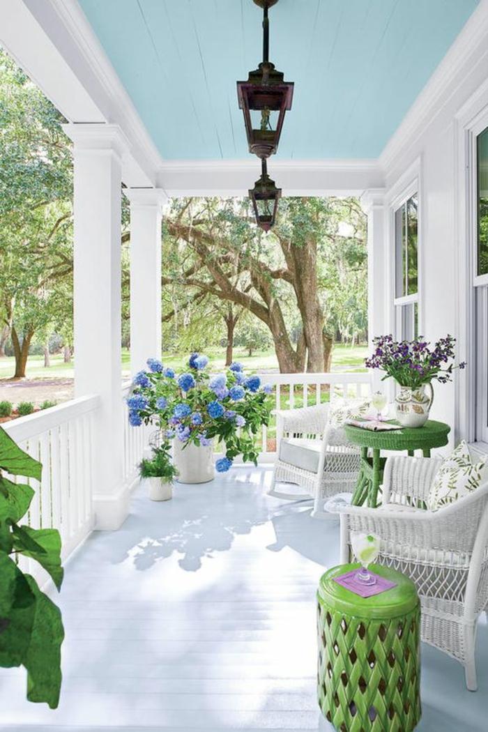 tarrazas con encanto, terraza blanca con techo azul, sillones y mesa redonda verde, flores decorativas
