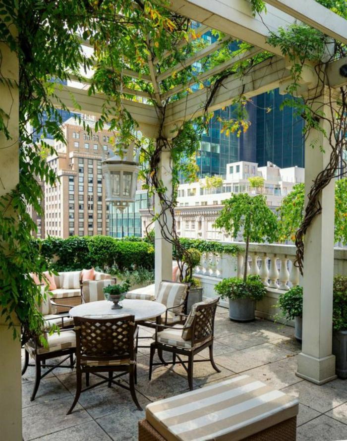 tarrazas con encanto, terraza en blanco, plantas trepadoras, mesa redonda y sillas con cojines, lámpara colgante