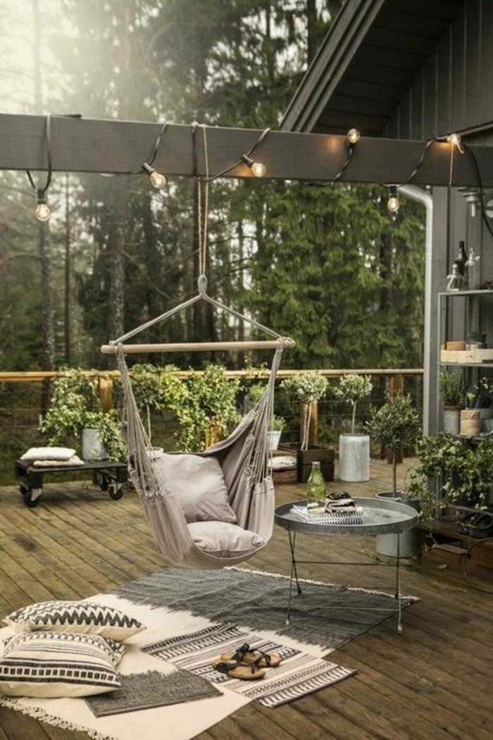 terrazas con encanto, terraza en gris y beige, suelo de madera, silla colgante, mesa redonda y plantas