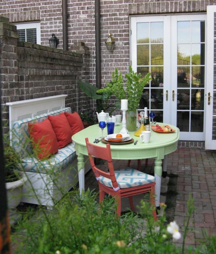 terrazas con encanto, terraza con mesa redonda verde, sofá con cojines rojos, candela y vasos
