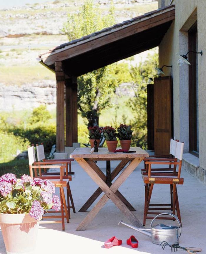 terrazas con encanto, terraza con mesa y sillas de madera, flores decoraticos y regadera, paisaje de montaña