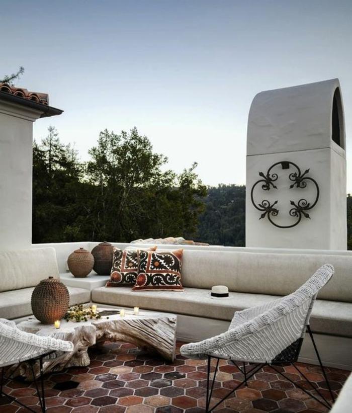 terrazas con encanto, terraza con suelo de baldosas, sofá y sillas, mesa de amdera natural, cojines y candelas