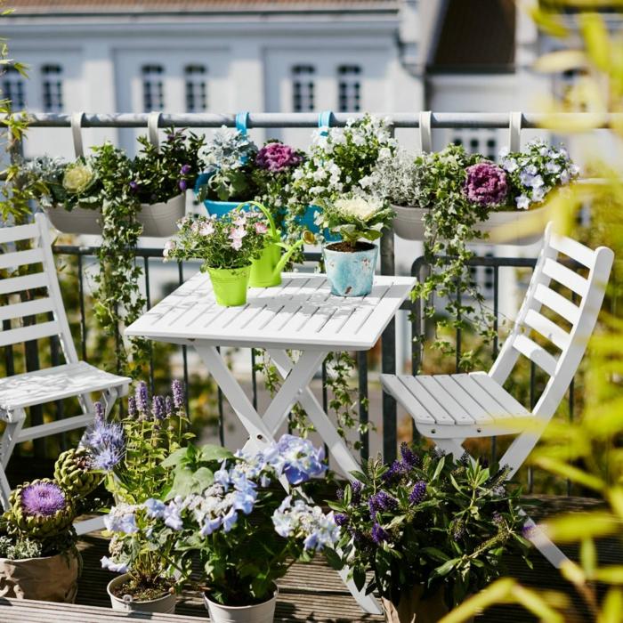 terrazas pequeñas, balcón lleno de flores, mesa y sillas de madera blanca