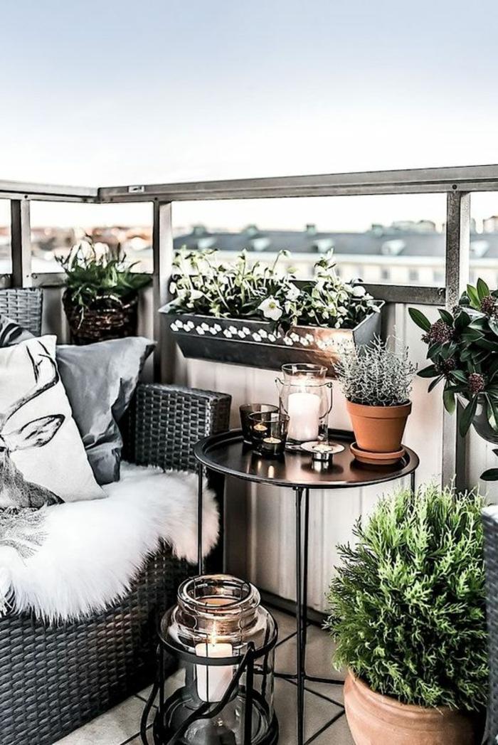 terrazas pequeñas, balcón con mesa redonda de metal, sillon de rattan con cojines, plantas y portavelas de cristal