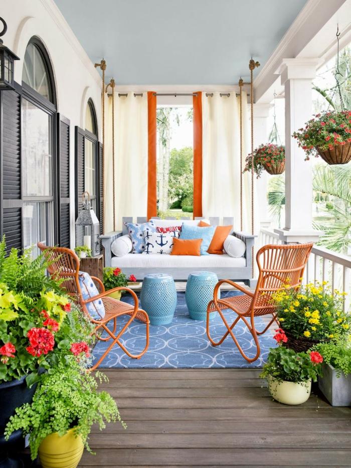 terrazas pequeñas, balcón con tarima, decoracion naranja y azul, sillas con cojines, macetas colgantes
