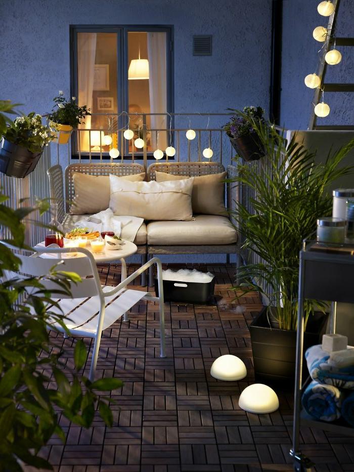 terrazas pequeñas, balcón con suelo de tarima, silla y sofá de metal con cojines, lámparas globos