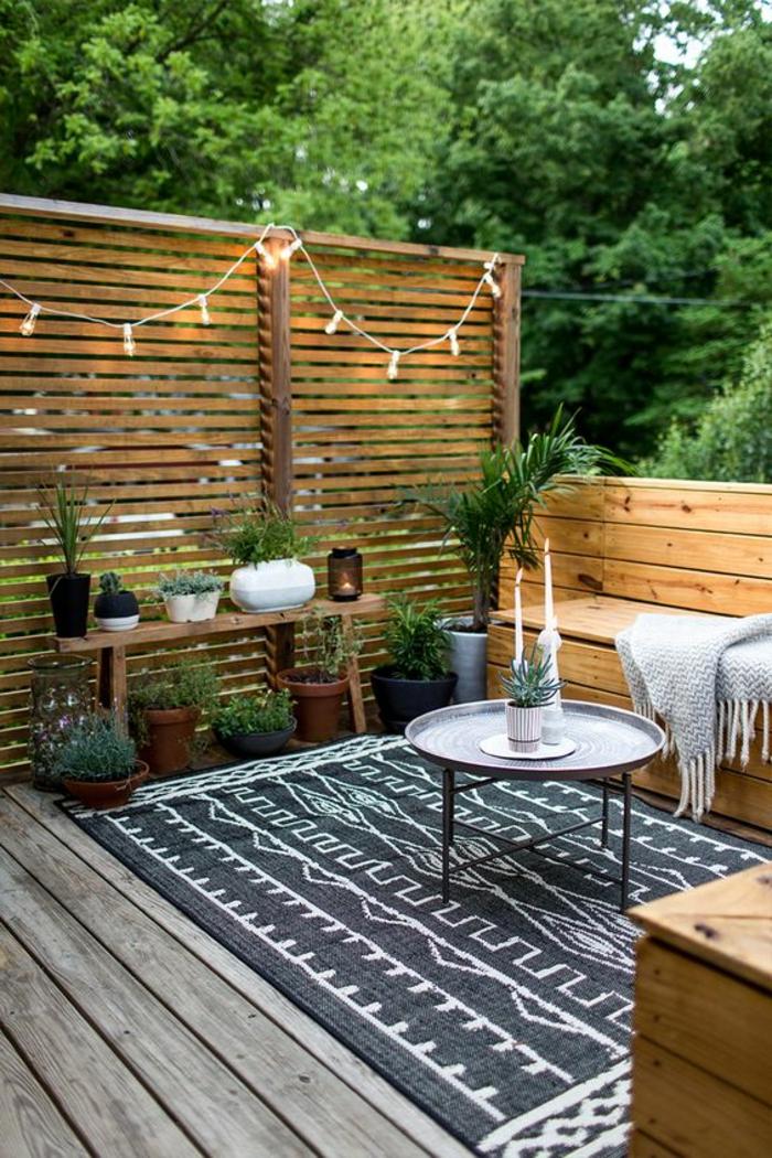 terrazas pequeñas, terraza de madera, mesa redonda de metal con portavelas, tapete blanco y negropç, banca y plantas