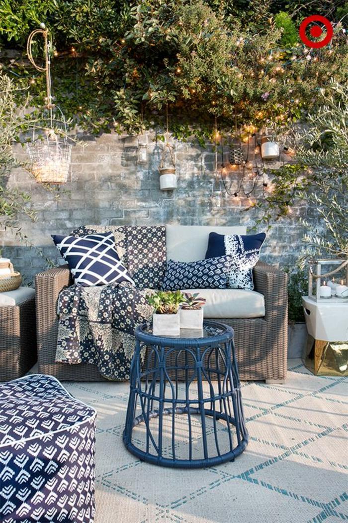 terrazas pequeñas, terraza en marrón y azul, sofá de rattan, mesita, pared de ladrillo con portavelas colgantes