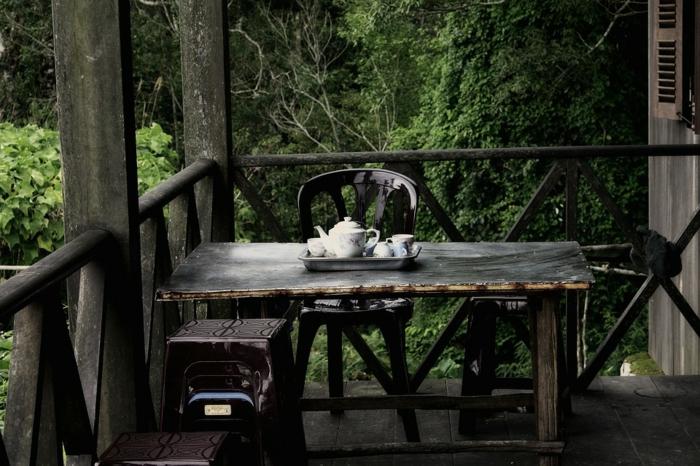terrazas pequeñas, terraza rústica, mesa de madra negra, silla de plñastico, tetera con tazas