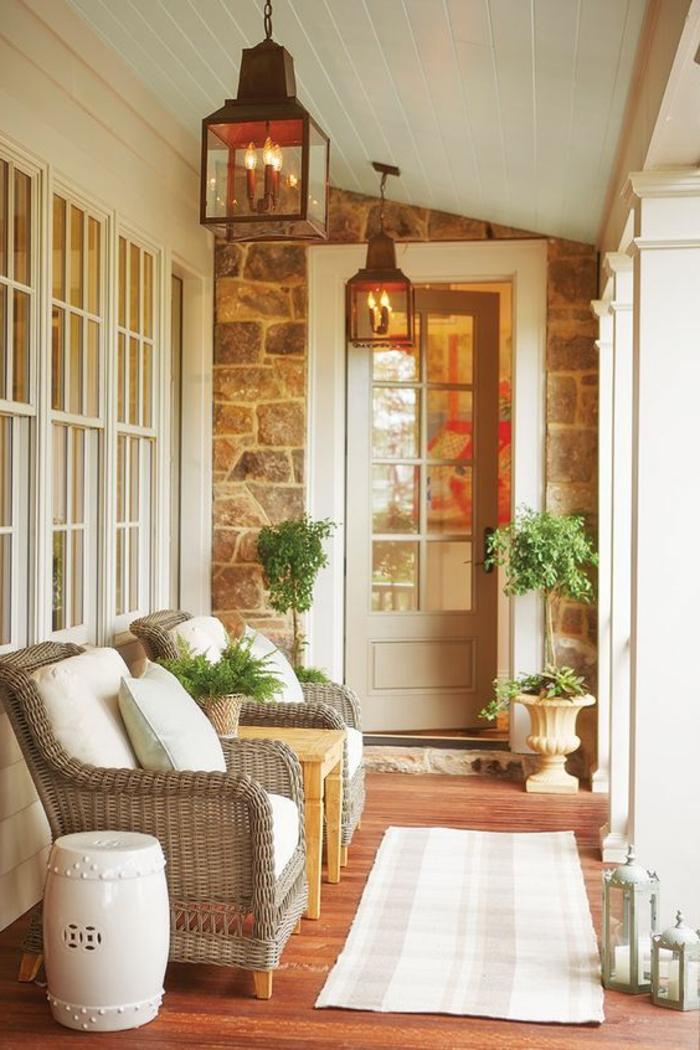 twrrazas pequeñas, terraza con suelo de tarima, sillones de rattan con cojines blancos, linternas colgantes, tapete