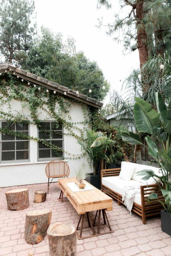 terrazas pequeñas, terraza con suelo de piedras, sillas de madera natural, sofá con cojines bñancos. planta trepadora