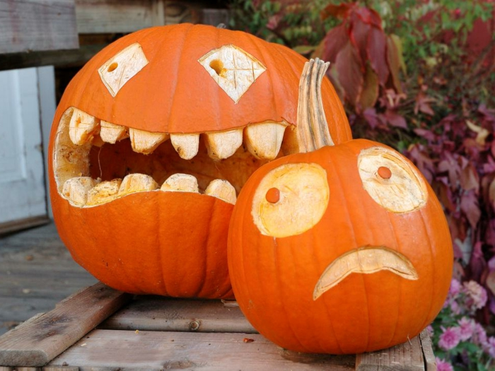 calabazas de halloween, dos calabazas talladas con caras terrorificas sobre madera