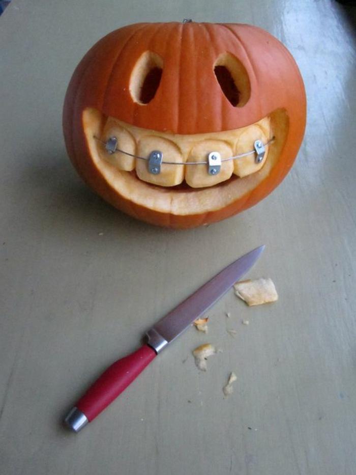 como vaciar una calabaza, cuchilloy calabaza tallada con dientes y brakets