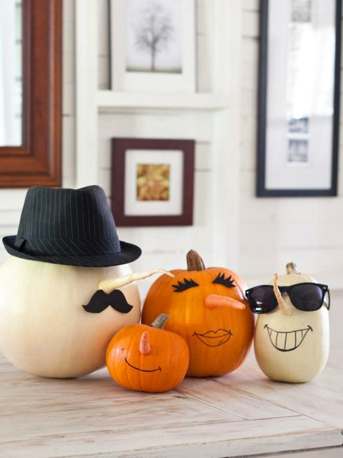 calabazas decoradas, calabazas en blanco y naranja pintadas con narices de zanahoria, gorro y gafas
