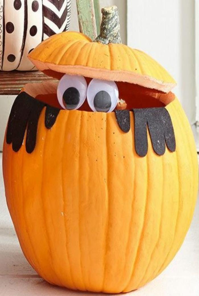 como vaciar una calabaza, calabaza color naranja tallada con ojos y manos negras